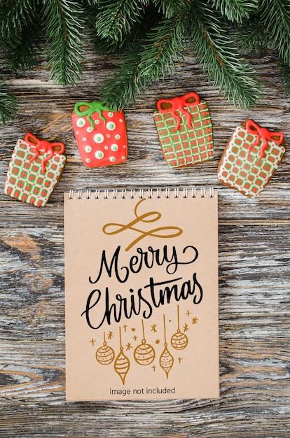 갈색 노트북 모형, 진저 쿠키 및 전나무 트리 크리스마스 배경 프리미엄 PSD 파일