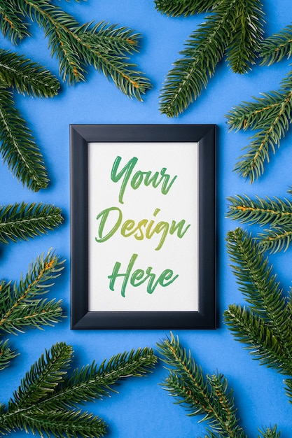 Christmas composition with empty picture frame and fir branches Premium Psd