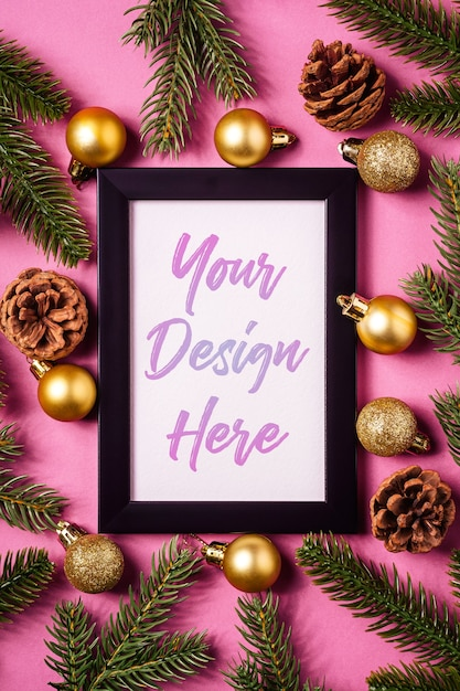Christmas composition with empty picture frame, golden christmas balls, pine cones and fir branches Premium Psd