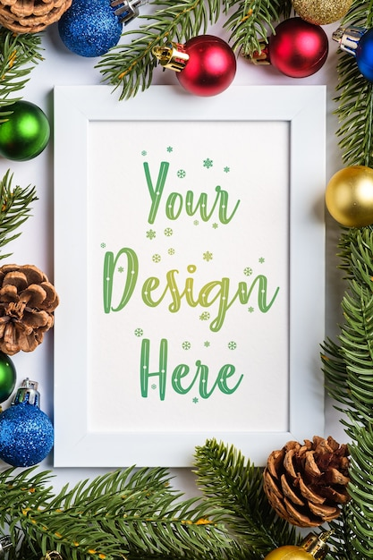 Christmas composition with empty picture frame with colorful balls, pine cones and fir needles Premium Psd