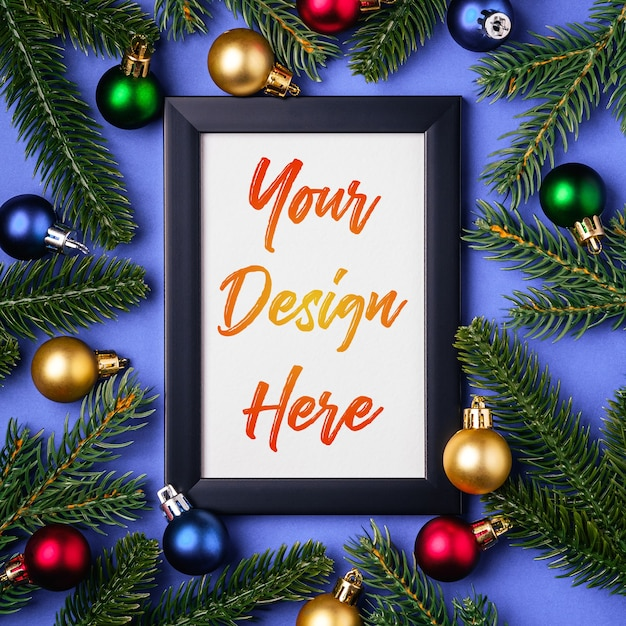 Christmas composition with empty picture frame with colorful ornaments and  fir branches Premium Psd