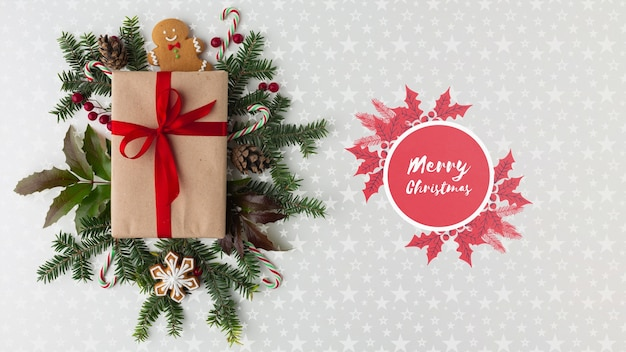 Christmas composition with green leaves and gift top view Free Psd