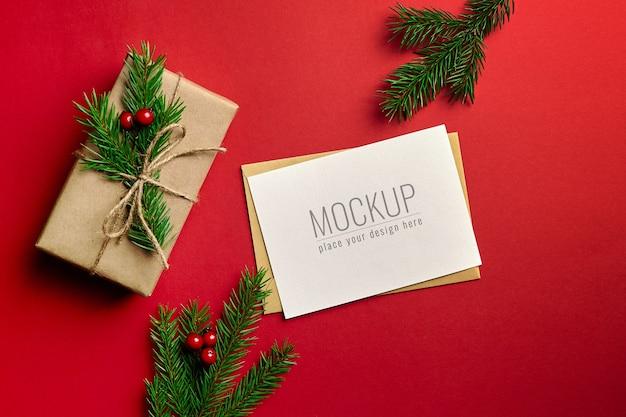 빨간색 배경에 장식 된 선물 상자와 전나무 나무 가지와 크리스마스 인사말 카드 모형 프리미엄 PSD 파일
