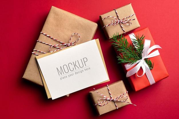 装飾されたギフトボックスの紙の背景とクリスマスグリーティングカードのモックアップ Premium Psd