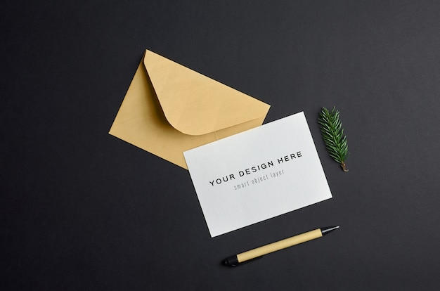 어두운 종이 배경에 봉투와 전나무 나무 나뭇 가지와 크리스마스 인사말 카드 모형 프리미엄 PSD 파일