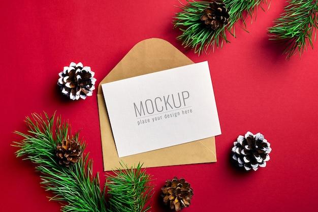Рождественский макет поздравительной открытки с конвертом и ветвями сосны с шишками Premium Psd