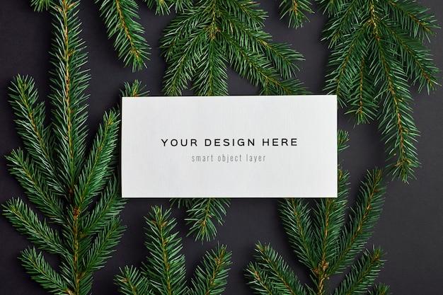 黒のモミの木の枝とクリスマスグリーティングカードのモックアップ Premium Psd