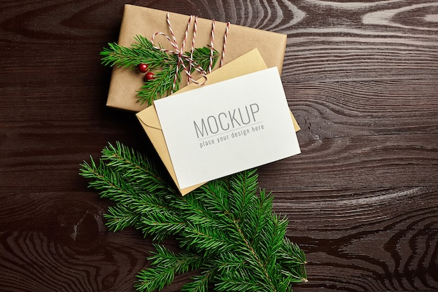 나무 배경에 선물 상자와 전나무 나무 가지와 크리스마스 인사말 카드 모형 프리미엄 PSD 파일