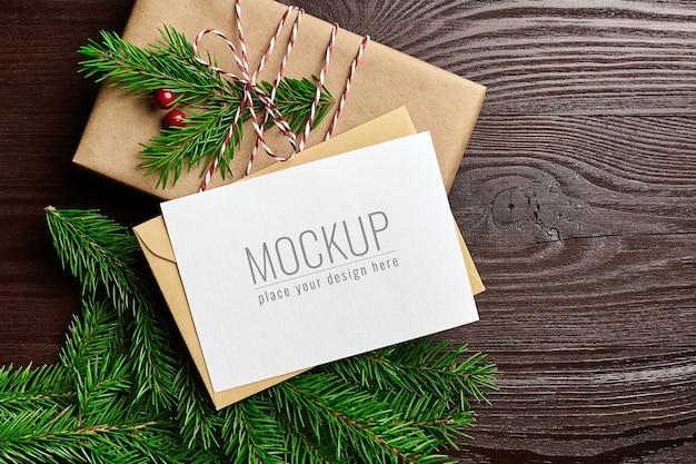 ギフトボックスと木製の背景にモミの木の枝とクリスマスグリーティングカードのモックアップ Premium Psd