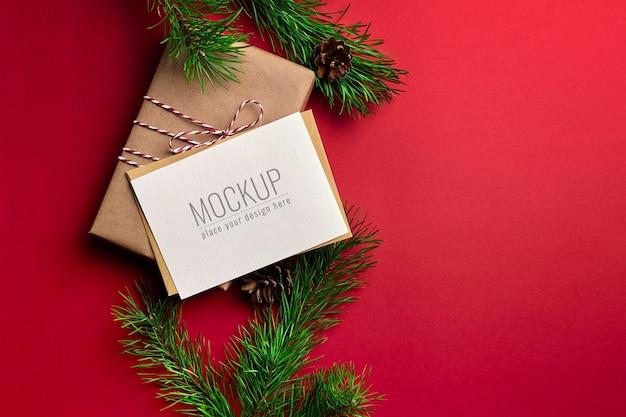 선물 상자와 빨간색 배경에 소나무 나무 가지 크리스마스 인사말 카드 모형 프리미엄 PSD 파일