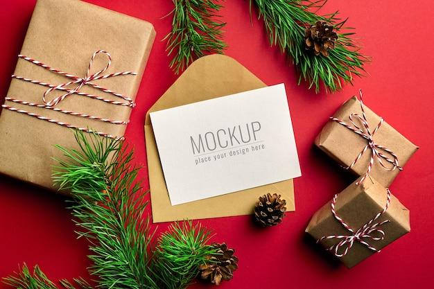 선물 상자와 소나무 나무 가지와 크리스마스 인사말 카드 모형 프리미엄 PSD 파일