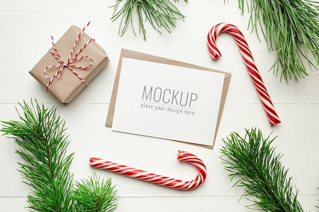 선물 상자, 사탕 지팡이 및 소나무 나뭇 가지와 크리스마스 인사말 카드 모형 프리미엄 PSD 파일