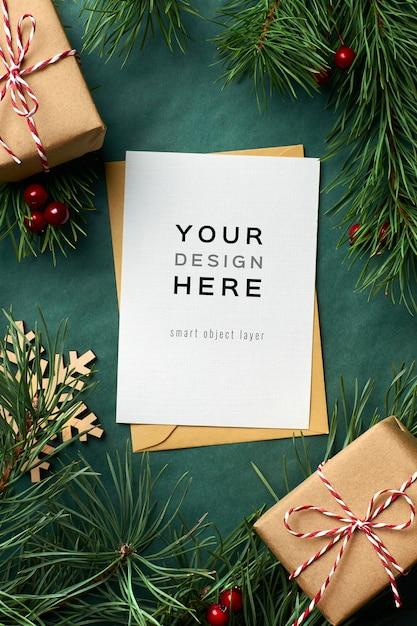 緑の背景に松の木の枝とギフトボックスとクリスマスグリーティングカードのモックアップ Premium Psd