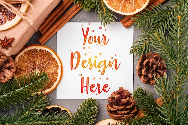 Christmas mockup composition. gift box, cinnamon, anise, dried fruits, pine cones and fir needles decorations on grey background Premium Psd