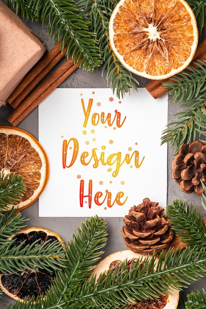 Рождественский макет композиции с подарочной коробкой, корицей, анисом, сухофруктами, сосновыми шишками и украшениями из хвои на сером Premium Psd