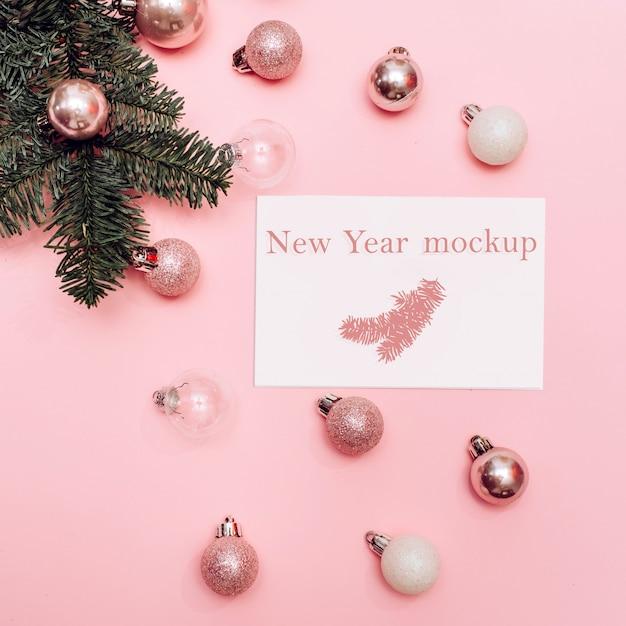 クリスマスのモックアップ、ピンクの背景に白とピンクのボール、テキスト用の白いカードとスプルースの枝 Premium Psd