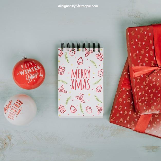 Рождественский макет с блокнотом и подарочными коробками Бесплатные Psd