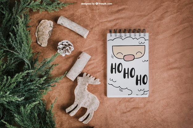 Christmas mockup with notepad next to fir Free Psd