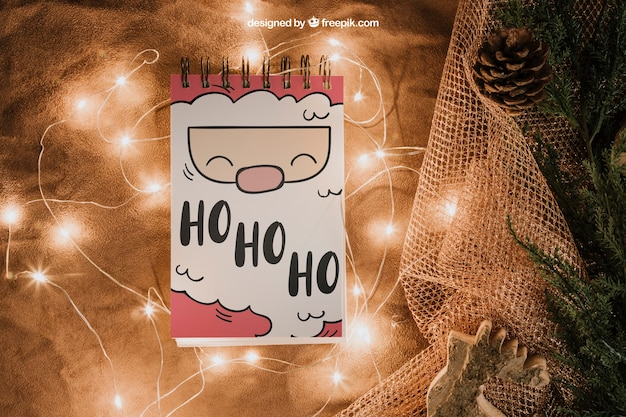 Christmas mockup with notepad and lights Free Psd
