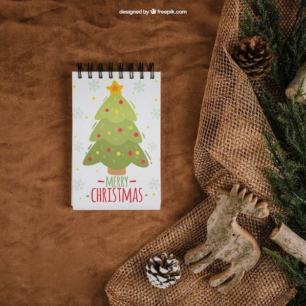 Christmas mockup with notepad on textile Free Psd