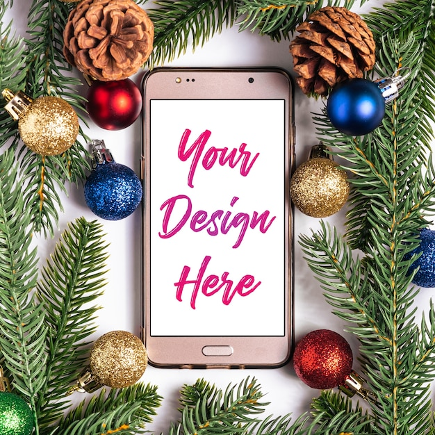Christmas online shopping. smartphone mockup with white blank screen. colorful balls, fir and pine cones decorations. Premium Psd