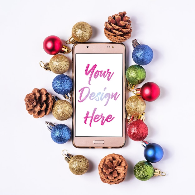 Christmas online shopping. smartphone mockup with white blank screen. colorful balls and pine cones decorations. Premium Psd