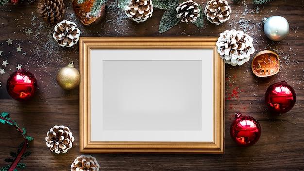 나무 배경에 크리스마스 장식과 클래식 골드 프레임 모형 무료 PSD 파일