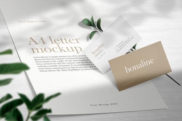 나무 바닥과 빛 그림자에 최소한의 비즈니스 카드와 편지 A4 모형을 청소하십시오. 프리미엄 PSD 파일