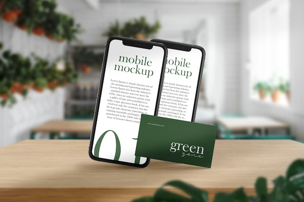 最小限の名刺と緑のカフェの木製テーブルと光の影のモバイルモックアップをきれいにします。 Premium Psd