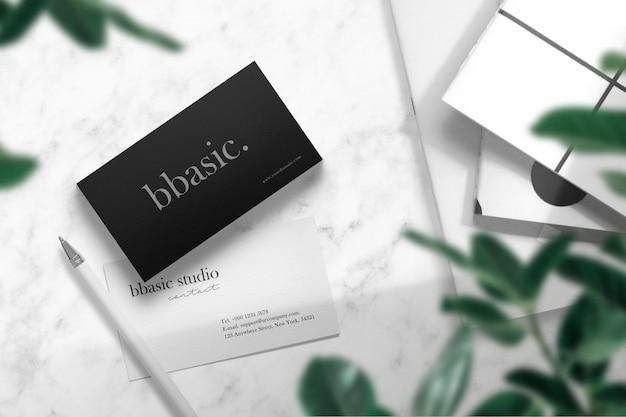 Чистый минимальный макет визитки на белом мраморе с книгами и ручкой Premium Psd