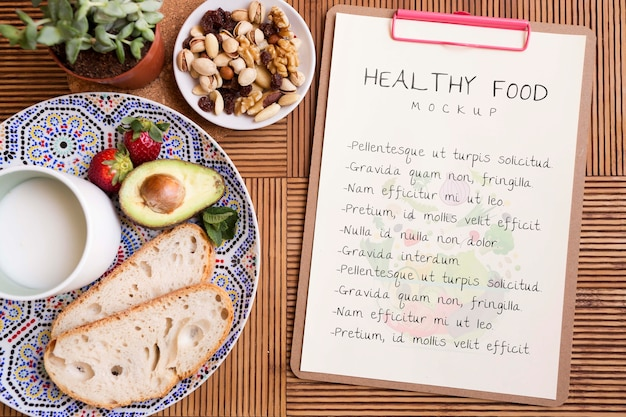 Clipboard beside plate with healthy food Free Psd