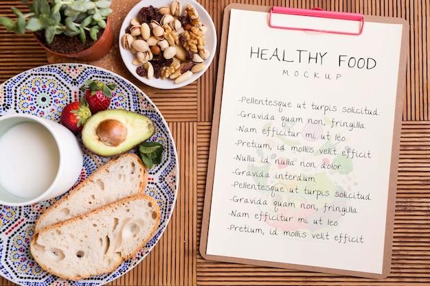 Буфер обмена рядом с тарелкой со здоровой пищей Бесплатные Psd