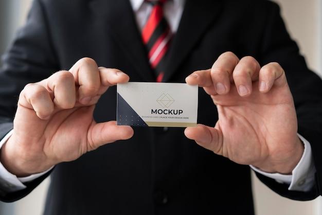 Uomo d'affari del primo piano che tiene il modello del biglietto da visita con entrambe le mani Psd Gratuite