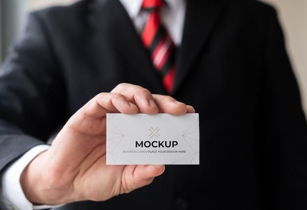 Uomo d'affari del primo piano che tiene il modello del biglietto da visita con una mano Psd Gratuite