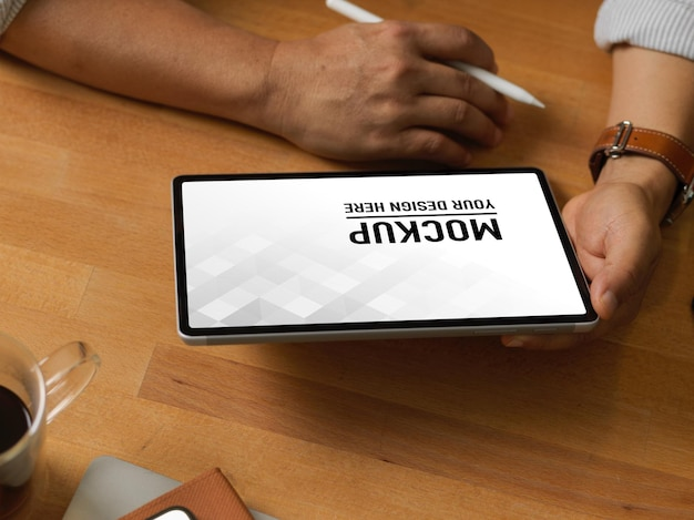 Close up of businessman using digital tablet mockup on wooden table Premium Psd