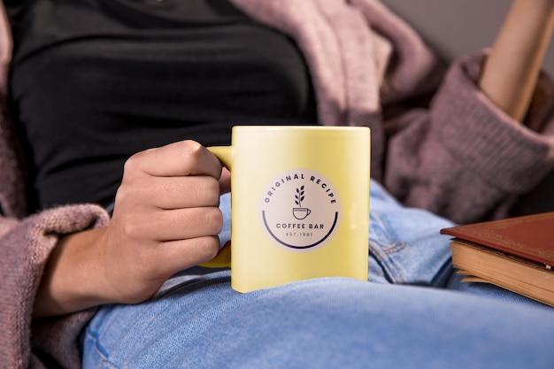 黄色のマグカップを保持しているクローズアップの女性 無料 Psd