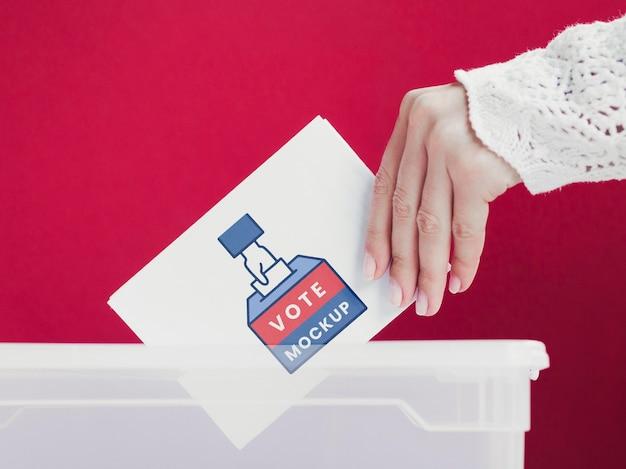 Женщина крупным планом кладет макет бюллетеня в коробку Бесплатные Psd