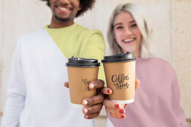 Close-up friends with hoodies and coffee cup Free Psd