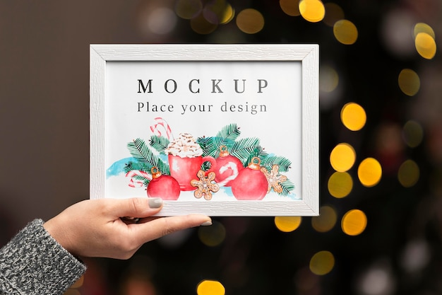 Close-up hand holding frame mock-up Free Psd