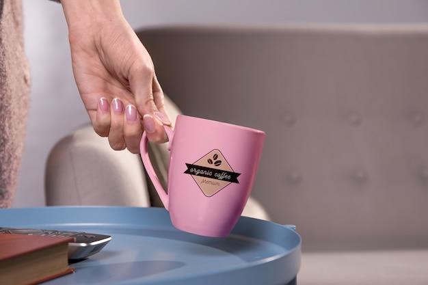 ピンクのコーヒー・マグを持っているクローズアップ手 無料 Psd