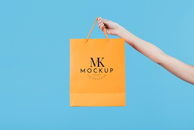 Close-up hand holding yellow paper bag Free Psd