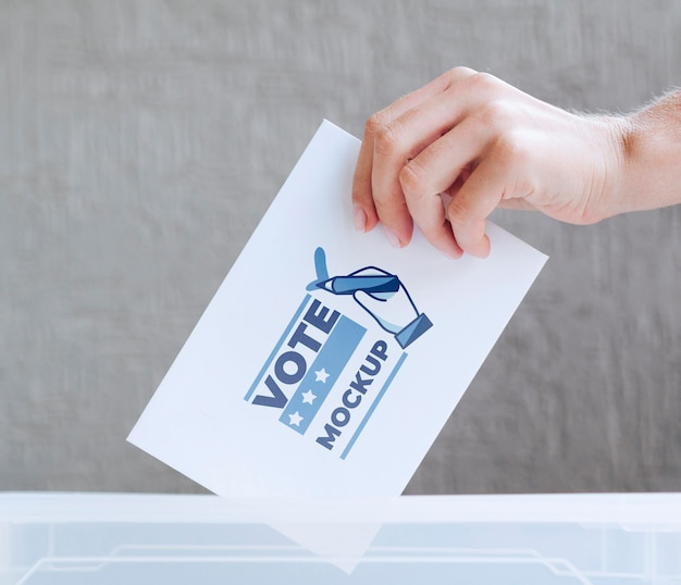Крупным планом рука положить макет бюллетеня в коробку Premium Psd
