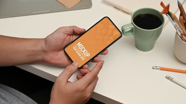 Close up on hands using smartphone mockup on workspace Premium Psd