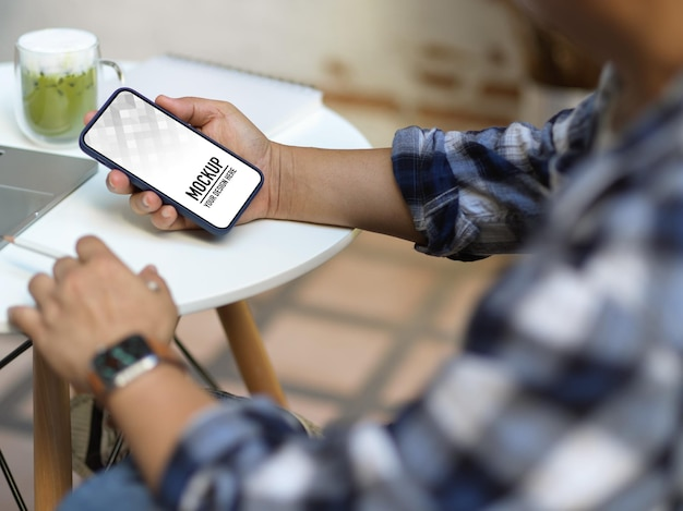 Close up of male hands using smartphone while sitting in office room Premium Psd
