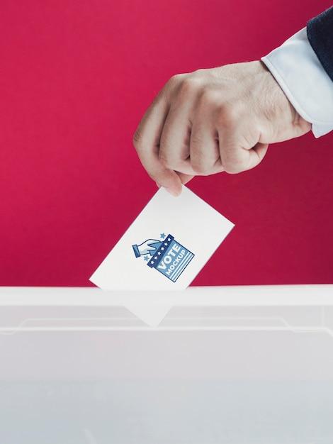 Крупным планом человек кладет макет бюллетеня в коробку Бесплатные Psd