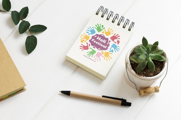 Close-up notepad next to plant Free Psd
