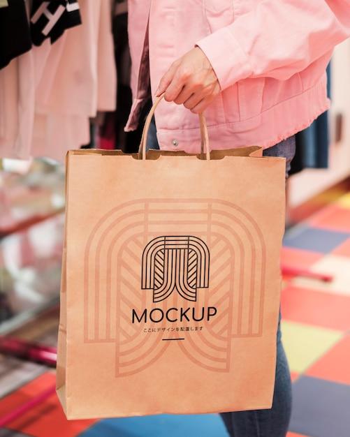 Persona del primo piano che tiene il sacchetto della spesa di mock-up Psd Gratuite