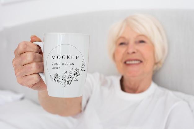 Close-up smiley woman holding mug Free Psd