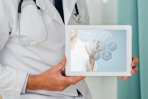Close-up tablet held by a doctor Free Psd