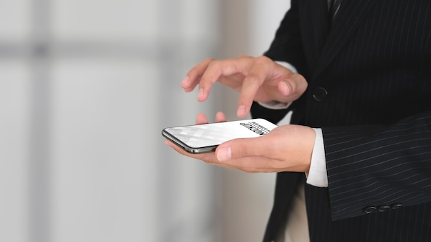 Close up view of businessman in black suit hands using smartphone mockup Premium Psd